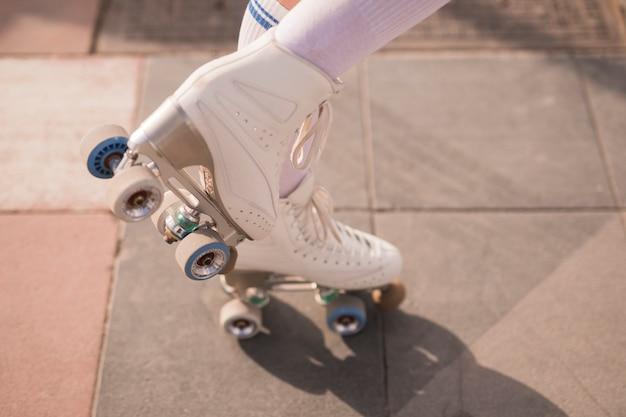 Niedriger abschnitt des weiblichen schlittschuhläufers mit weißem weinleserollschuh Kostenlose Fotos