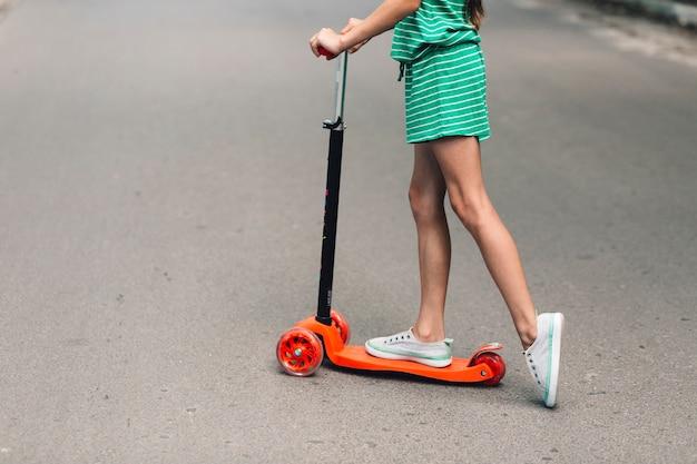 Niedriger abschnitt eines mädchenreitstoßrollers auf straße Kostenlose Fotos