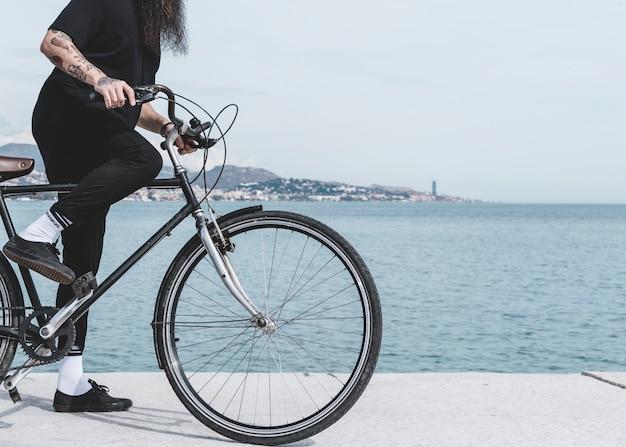 Niedriger abschnitt eines mannes, der fahrrad auf straße nahe dem hafen fährt Kostenlose Fotos