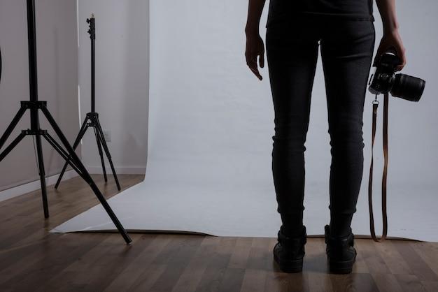 Niedriger abschnitt eines weiblichen fotografen, der kamera im fotostudio hält Kostenlose Fotos
