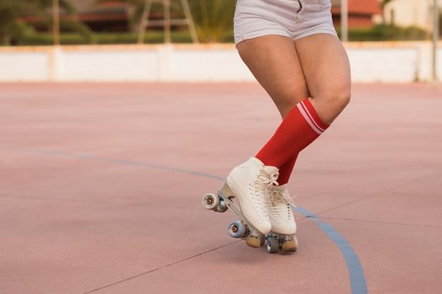 Niedriger abschnitt eines weiblichen schlittschuhläufers, der mit rollschuh auf gericht balanciert Kostenlose Fotos