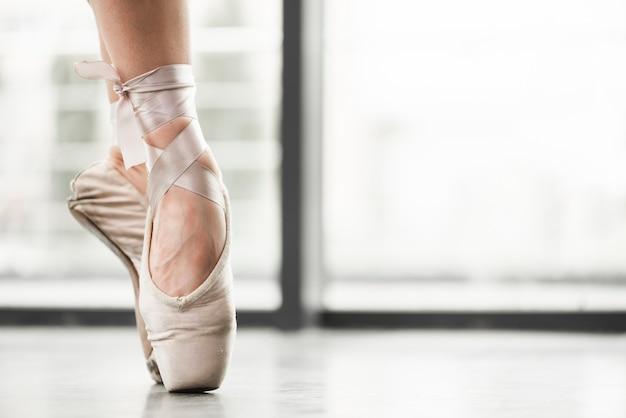 Niedriger abschnitt von den tragenden ballettschuhen des weiblichen tänzers, die an stehen, gehen auf den zehen Kostenlose Fotos