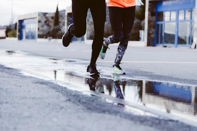 Niedriger abschnitt von zwei athleten, die auf straße laufen Kostenlose Fotos