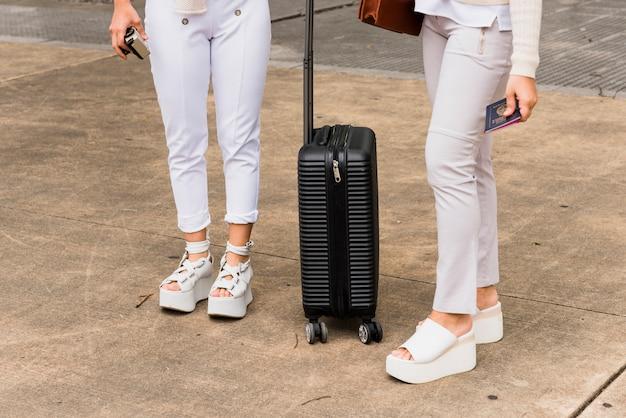Niedriger abschnitt von zwei jungen frauen, die mit schwarzem koffer stehen Kostenlose Fotos