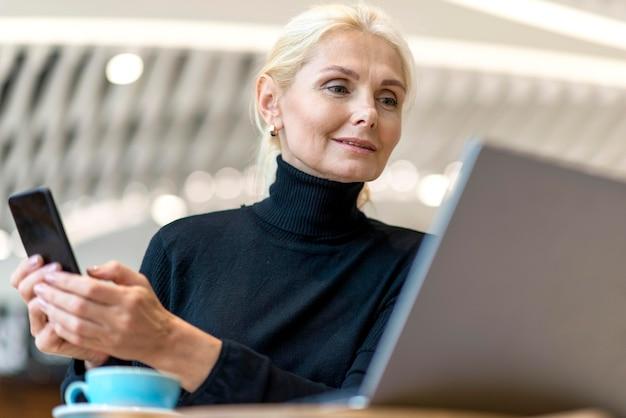 Niedriger winkel der älteren geschäftsfrau, die auf laptop mit smartphone arbeitet Kostenlose Fotos