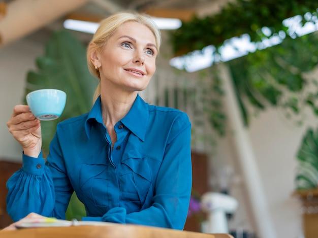 Niedriger winkel der älteren geschäftsfrau, die tasse kaffee während der arbeit hat Kostenlose Fotos