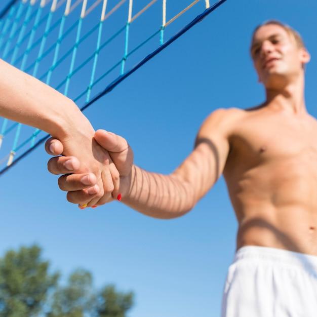 Niedriger winkel der volleyballspieler am strand hand schütteln unter dem netz Kostenlose Fotos