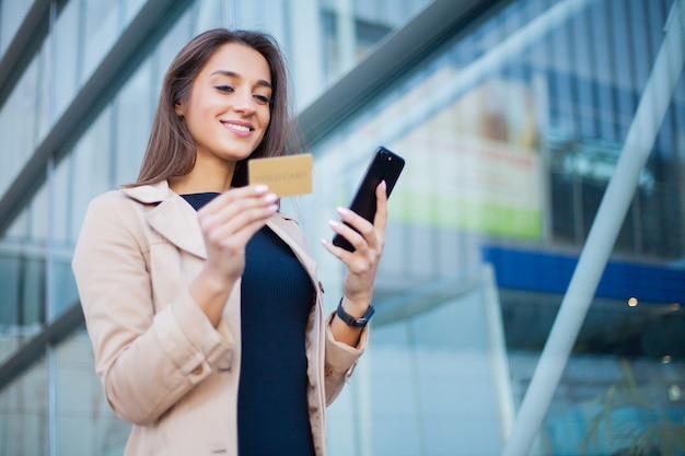 Niedriger winkel des erfreuten mädchens stehend an der flughafenhalle. er verwendet gold kreditkarte und handy für die zahlung Premium Fotos