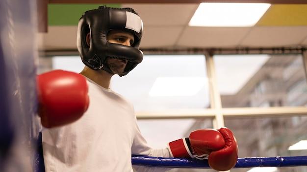 Niedriger winkel des männlichen boxers mit helm und handschuhen Kostenlose Fotos