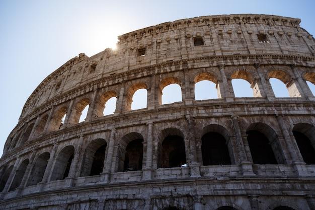 Niedriger winkelschuss des berühmten kolosseums in rom, italien unter dem hellen himmel Kostenlose Fotos