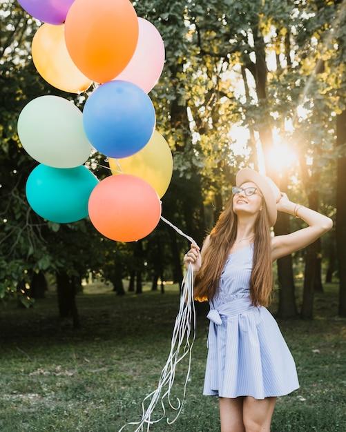 Niedriges winkelgeburtstagsmädchen mit ballonen im sonnenlicht Kostenlose Fotos
