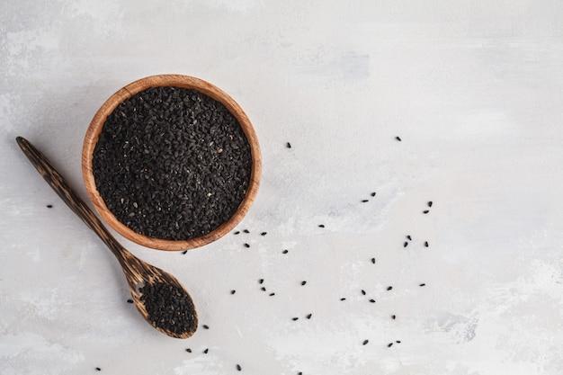 Nigella sativa oder schwarzkümmel in der hölzernen schüssel auf weißem hintergrund, kopienraum, draufsicht Premium Fotos