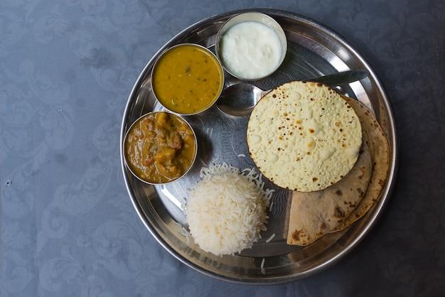 Nordindisches thali, eine tipical mahlzeit diente auf edelstahlplatte auf blauer tabelle Premium Fotos