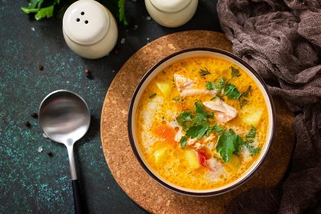 Norwegische suppe mit sahne und lachs auf einem rustikalen holztisch auf einem dunklen steinhintergrund Premium Fotos
