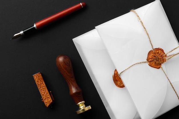 Notar wachsstempel. weißer umschlag mit braunem wachssiegel, goldener stempel. responsive design-modell, flach gelegt. stillleben mit postzubehör. Premium Fotos