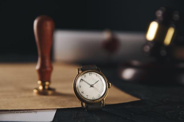 Notarstempel und holzhammer mit uhr auf dem tisch Premium Fotos