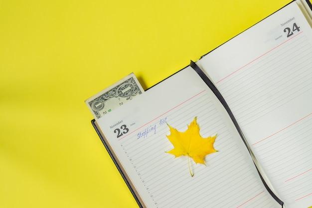 Notebook auf gelb. einkaufsliste an schwarzem freitag und ein bookmark des dollars. Premium Fotos