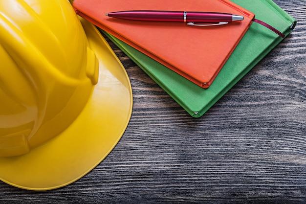 Notepads kugelschreiber-sicherheits-schutzhelm auf holzbrett-konstruktionskonzept Premium Fotos