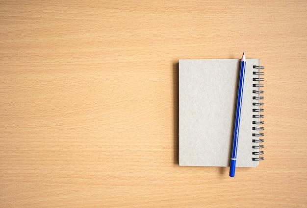 Notizblock mit bleistift auf holzbrett Premium Fotos
