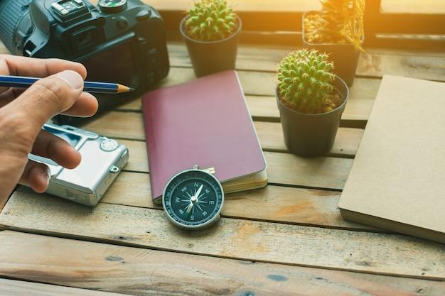 Notizblock mit pass, kamera und smartphone auf holz Premium Fotos