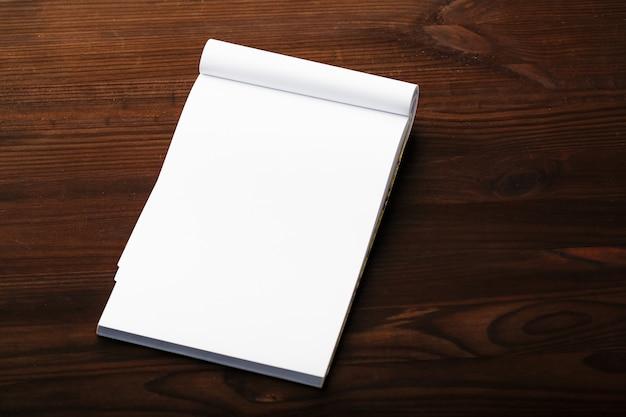 Notizblock mit rotem bleistift auf einem braunen holztischhintergrund, für bildung, schreiben ziele und taten Premium Fotos