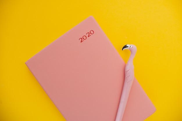 Notizblock und flamingo stift auf einem gelben abstrakten hintergrund mit kopie raum, Premium Fotos
