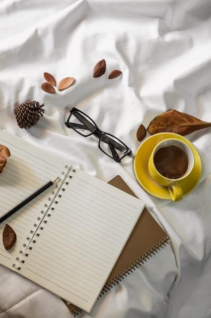 Notizblockbrief-tasse kaffee und ein buch mit einer decke auf einem weißen gewebe im bett. Premium Fotos