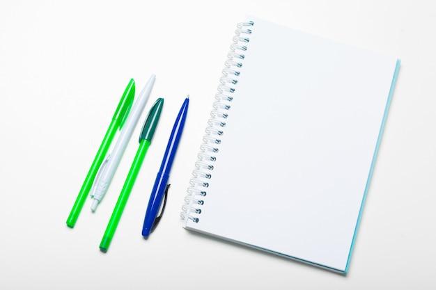 Notizblocknotizbuch und kugelschreiber lokalisiert auf weißem hintergrund Premium Fotos