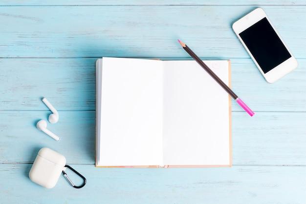 Notizbuch aus papier für notizen, modernes smartphone und kopfhörer Premium Fotos
