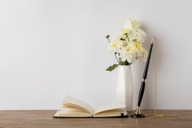 Notizbuch aus papier mit stift und blumenvase auf dem arbeitstisch. Premium Fotos