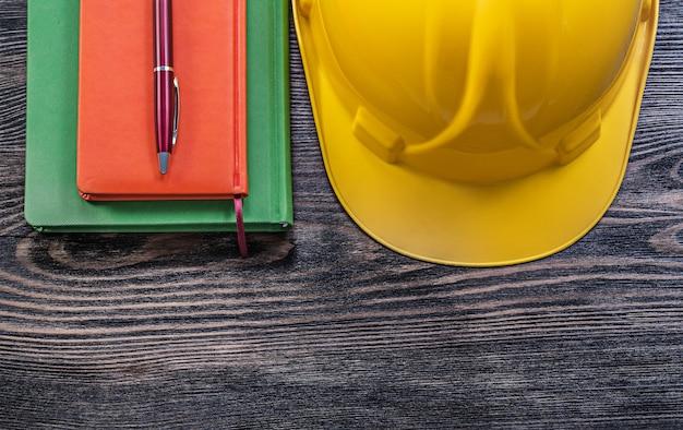 Notizbuch kugelschreiber schutzhelm auf holzbrettkonstruktionskonzept Premium Fotos