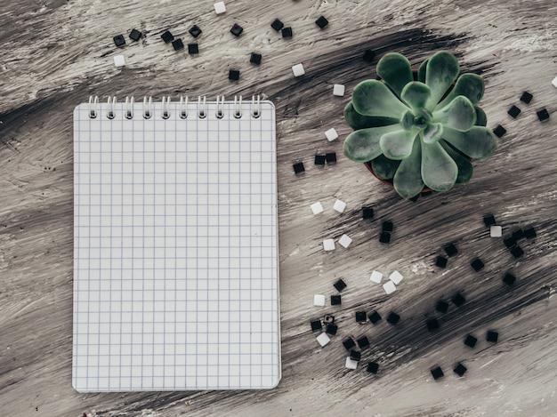 Notizbuch mit blume auf grauer tabelle. flach liegen. Premium Fotos