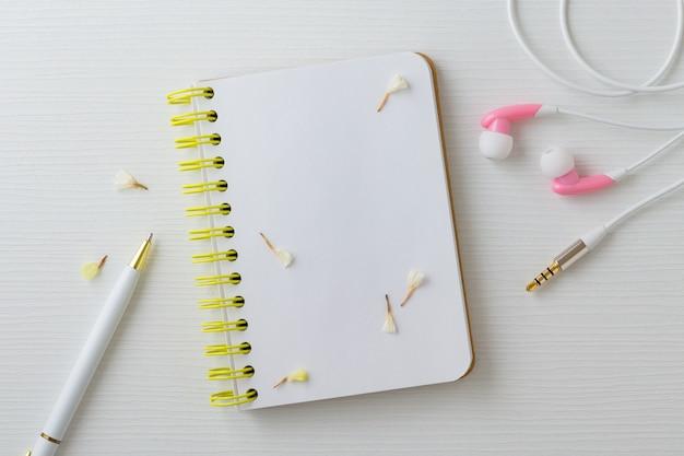 Notizbuch mit blumenkopfhörer und -stift Premium Fotos