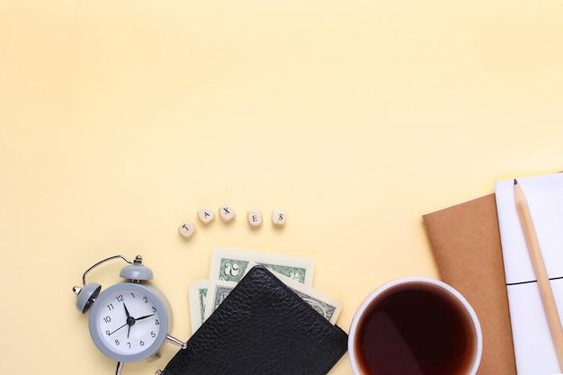 Notizbuch mit einem bleistift, einer geldbörse, einem wecker, einem tasse kaffee auf einem beige hintergrund mit den wortsteuern von hölzernen buchstaben. Premium Fotos