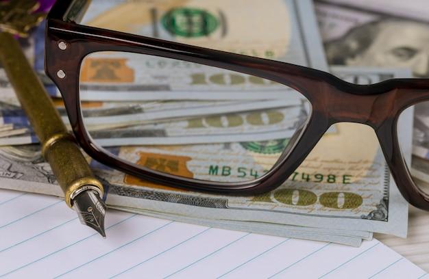 Notizbuch mit finanzgeschäftsbuchhaltung der dollar, des stiftes und der gläser Premium Fotos