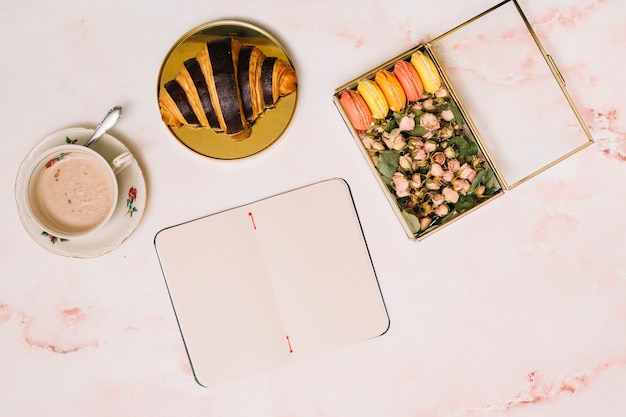 Notizbuch mit hörnchen und kasten mit blumen auf tabelle Kostenlose Fotos