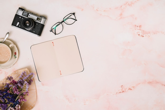 Notizbuch mit kaffeetasse, kamera und gläsern auf tabelle Kostenlose Fotos