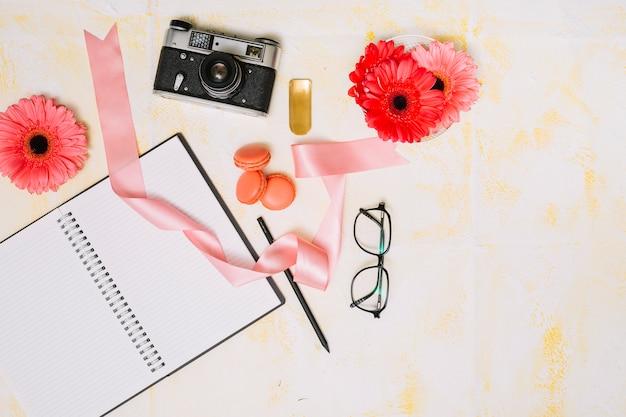 Notizbuch mit kamera, blumen und band auf leuchttisch Kostenlose Fotos
