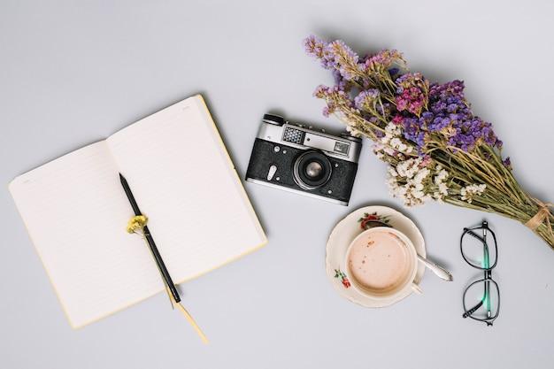 Notizbuch mit kamera und blumen auf tabelle Kostenlose Fotos