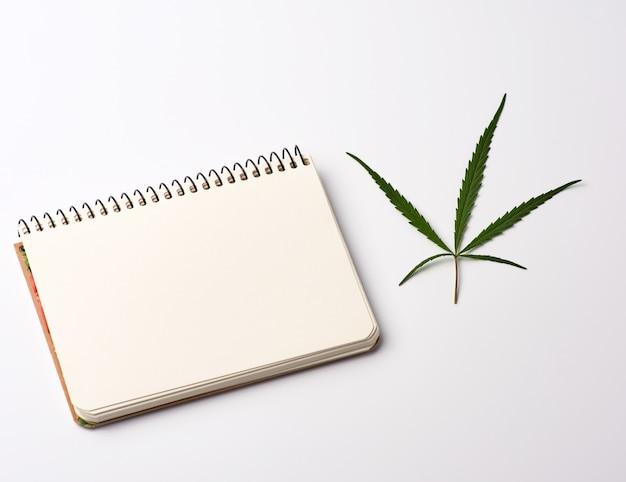 Notizbuch mit leeren weißen blättern und grünem hanfblatt Premium Fotos