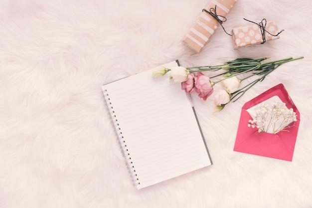 Notizbuch mit rosen, geschenken und umschlag auf heller decke Kostenlose Fotos