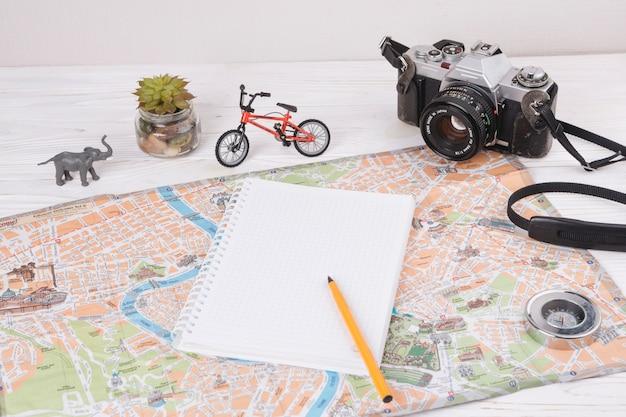 Notizbuch mit stift auf karte nahe spielzeugtier, -kamera und -fahrrad Kostenlose Fotos