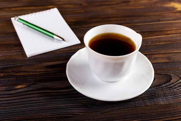 Notizbuch mit stift und kaffeetasse, geschäftskonzept Premium Fotos