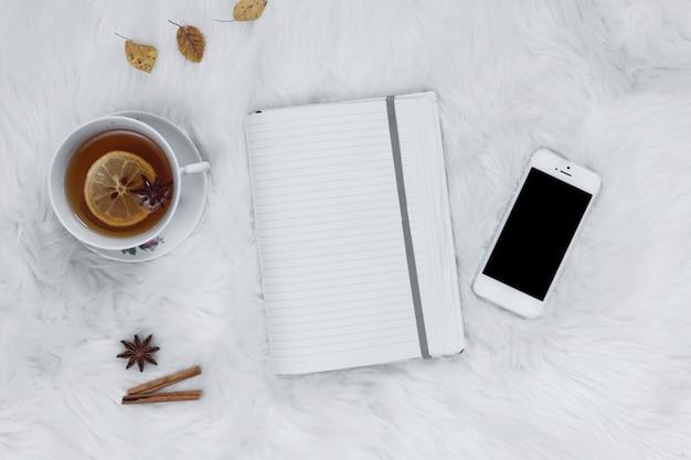 Notizbuch mit teetasse nahe smartpone auf plaid Kostenlose Fotos