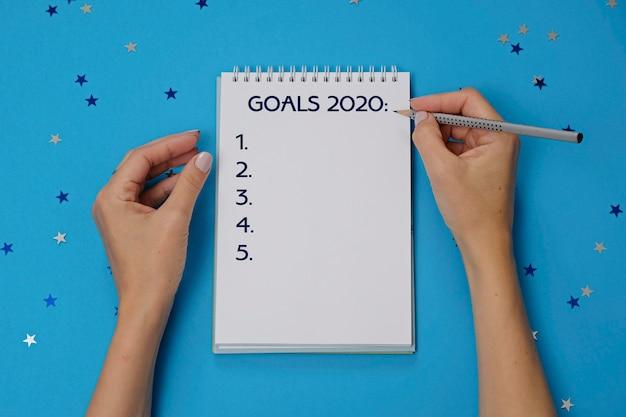 Notizbuch mit text zielen 2020 und weiblichen händen mit bleistift Premium Fotos