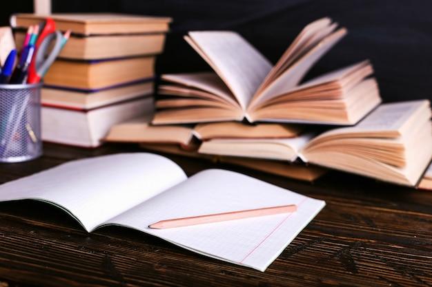 Notizbuch, offene bücher und schulbedarf auf einem dunklen holztisch vor dem hintergrund eines kreidebrettes Premium Fotos