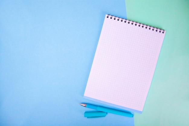 Notizbuch, stift auf blauem hintergrund. Premium Fotos