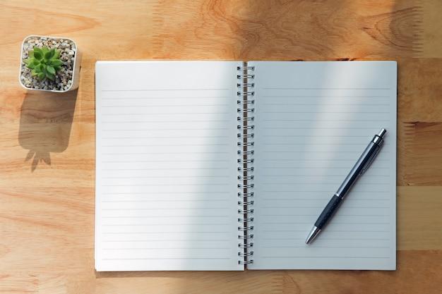 Notizbuch, stift, grünpflanze auf hölzernem hintergrund Premium Fotos