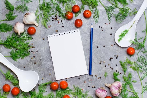 Notizbuch und bleistift für das schreiben von rezepten umgeben durch kirsche, dill, pfeffergewürz, knoblauch und schöpflöffel auf einem grauen hintergrund. Premium Fotos