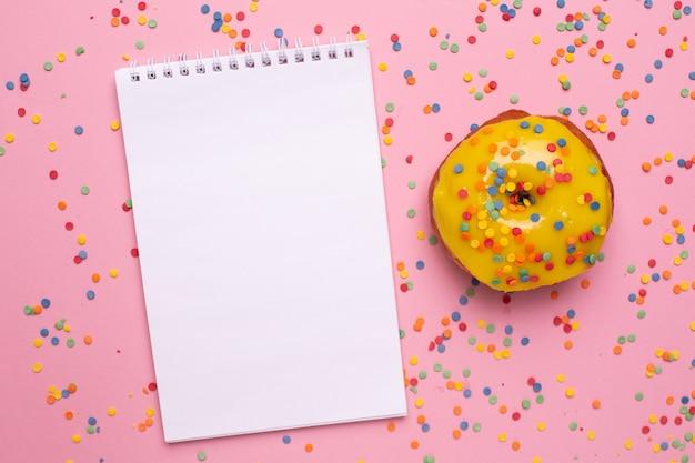 Notizbuch und gelber süßer donut auf einer rosa hintergrundebenenlage Premium Fotos